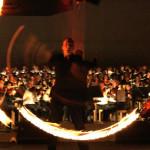 Feuerkünstler mit Fackelschwingen und life Orchester
